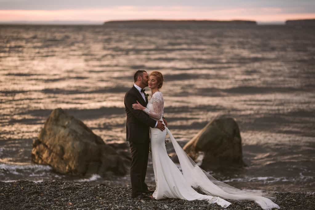 A groom is kissing a bride on the cheek. They are on Topsail beach, with two big rocks behind them. It is sunset and the water is beautiful and soft; Bell Island is behind them wrapped in the pink of the sky.