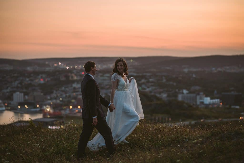 A bride and groom walk in a field of wildflowers - it is dusk, and they are looking at each other. The sky is orange, and in the background the lights of St. John's harbour are twinkling.