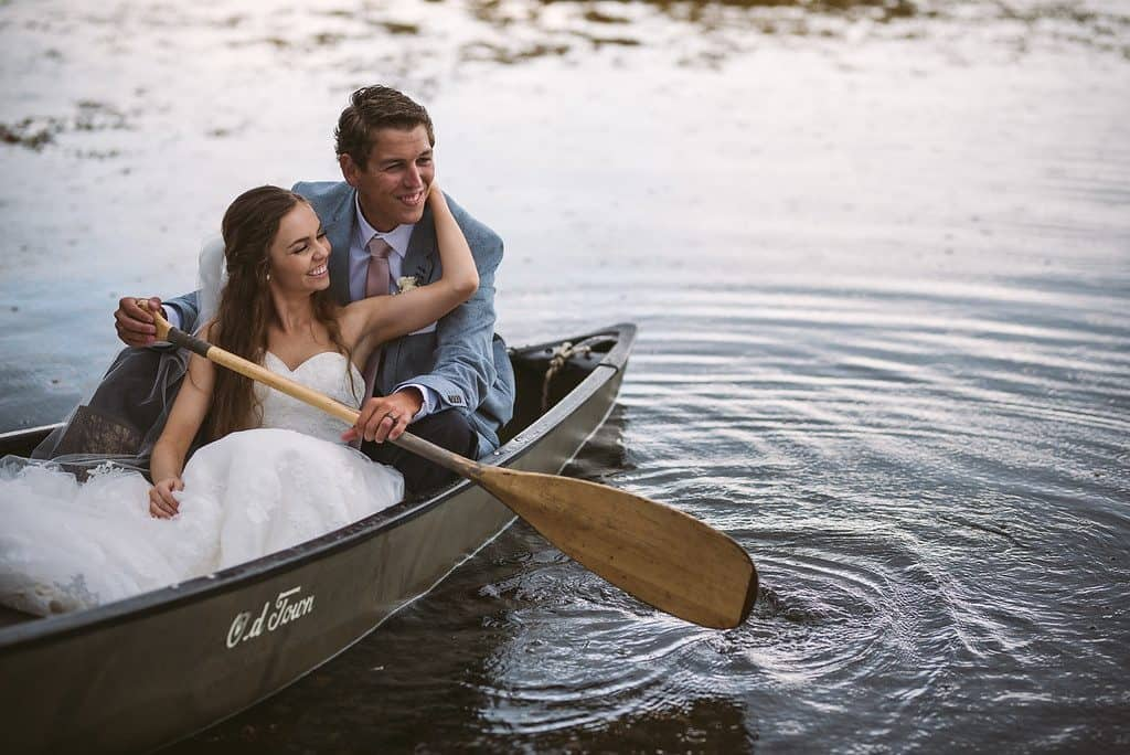 A newly married couple sits in a canoe in the ocean. He is holding an oar and her arm is around her neck. They are both laughing. In Embree, Newfoundland