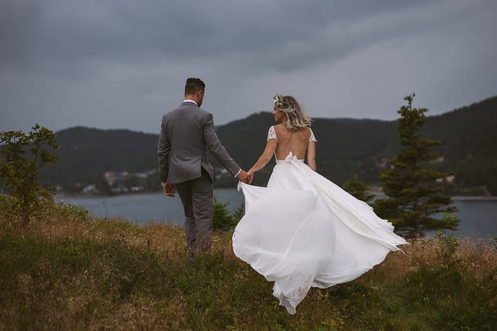 a wedding couple walks through a field near the ocean while her dress blows in the wind. Wedding in bay roberts, newfoundland