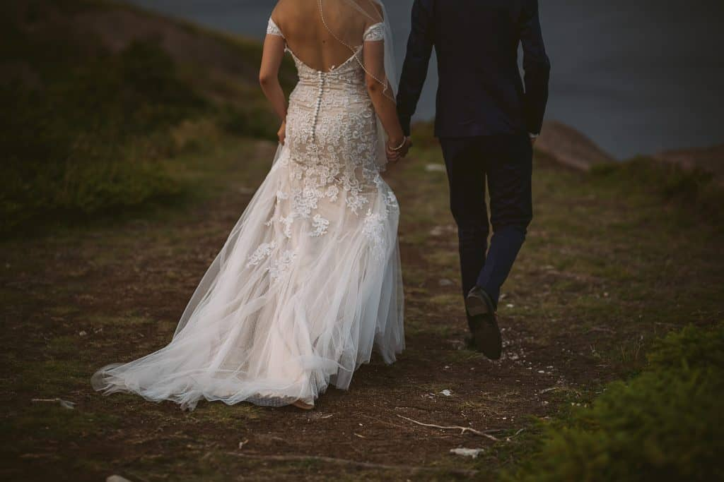 A couple is holding hands while walking - the image is taken from the neck down so you cannot see their faces. The bride's dress is dragging on the ground. In the distance is ocean.