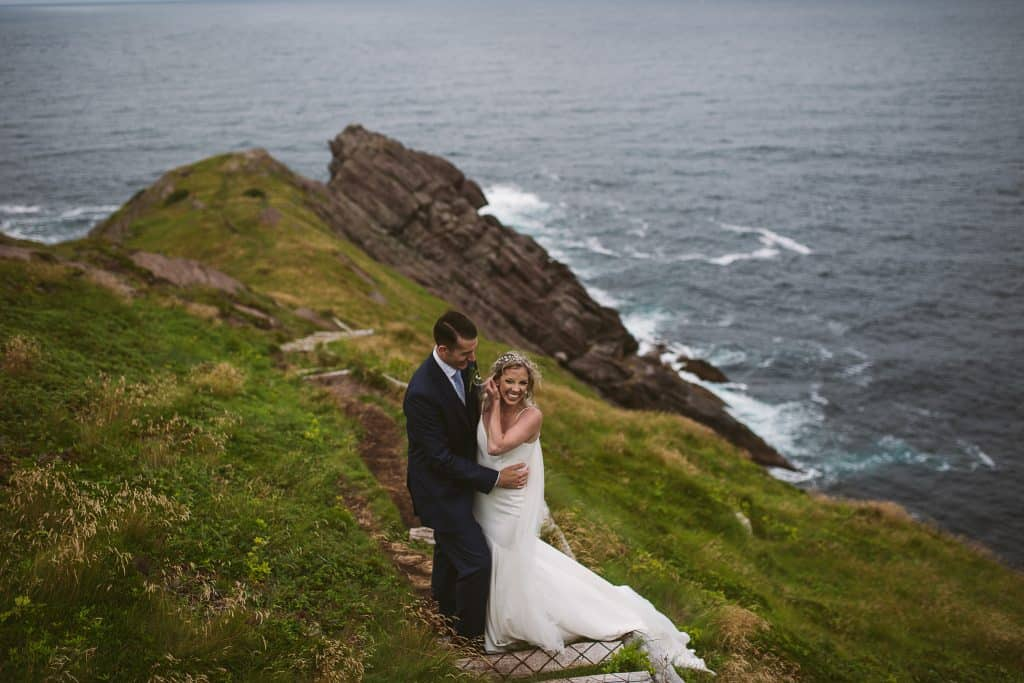 A groom is holding onto a bride as she laughs and fixes her hair. They are standing on the Torbay Point portion of the east coast trail, with the fingers of the rocks fading away behind them.