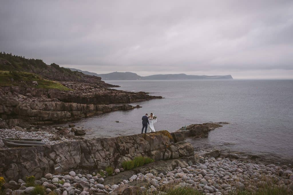 A couple are walking on a long rock in the ocean near Blackead, NL. It is foggy and the sky is a deep purpley-blue.