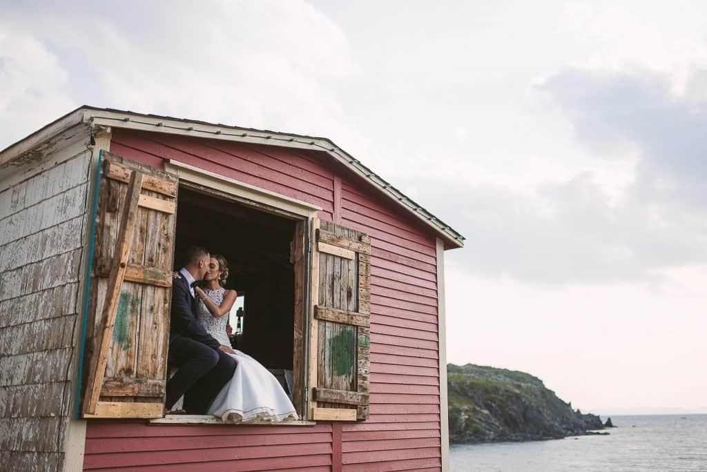 A couple sits in a doorway that leads to nowhere while the doors are wide open - they are on the top floor of a red stage, and the image is looking up at them as they kiss. Around them is ocean and cliffs.