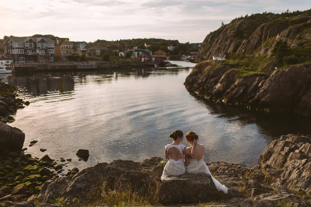 Two brides are embracing while sitting on a rock. One has a dress with an open back, the other has a lace and tulle dress. Quidi Vidi Village is behind them, the ocean has soft, pink waves.