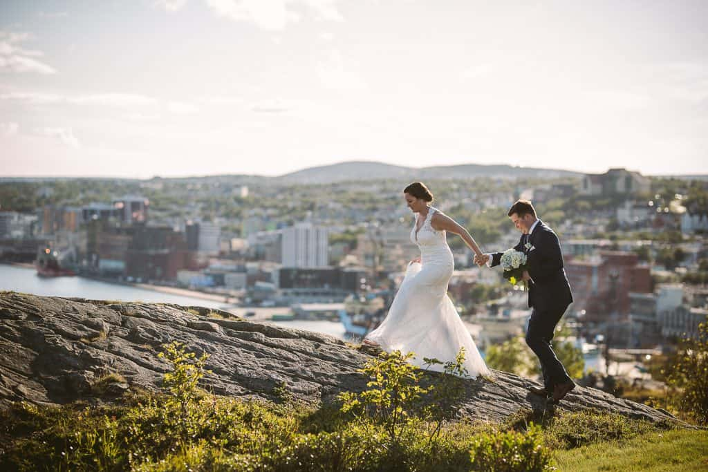 A bride leads her groom up a hill. He is holding her bouquet and her dress is hiked up. In the background is St. John's Harbour.