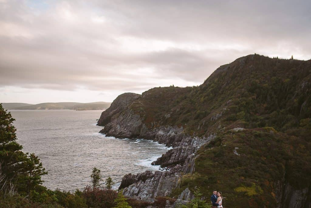 A landscape image shows the cliffs near Cuckhold's Cove, St. John's - in the bottom right corner, a couple embraces. It is sunset and the waves are hitting the cliffs under a soft purple sky.