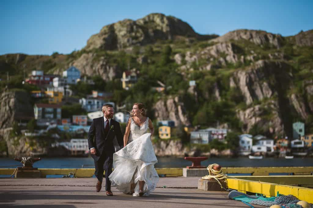 A wedding couple runs on a wharf, laughing at each other. In the background are the cliffs of the St. John's Battery with all the colourful houses. It's a bright sunny day and they are laughing.
