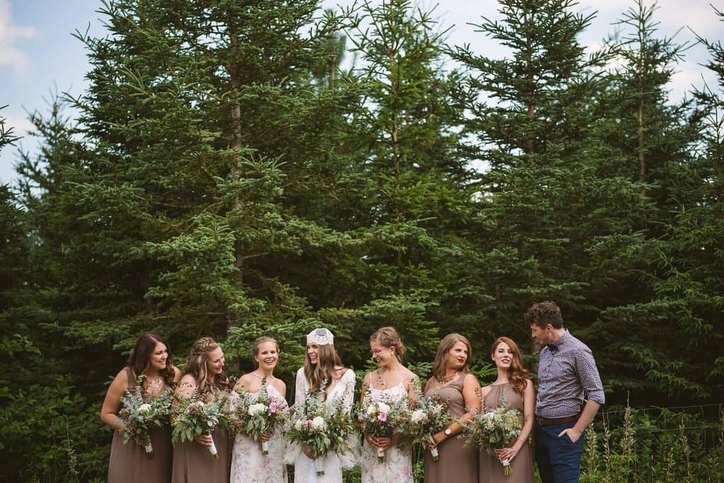 A bride and her bridesmaids (and bridesman) are looking at each other and laughing in a forest.