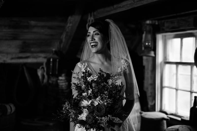 The image is black and white. A bride is in a shed holding a large bouquet - she is laughing loudly and looking out of the frame. A window is behind her and old wooden barrels around her.