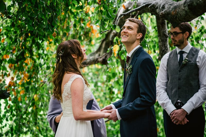 A couple stands under a large tree during their ceremony. The groom is looking off in the distance holding back tears. The bride is looking at him with a large smile on her face. They are holding hands.