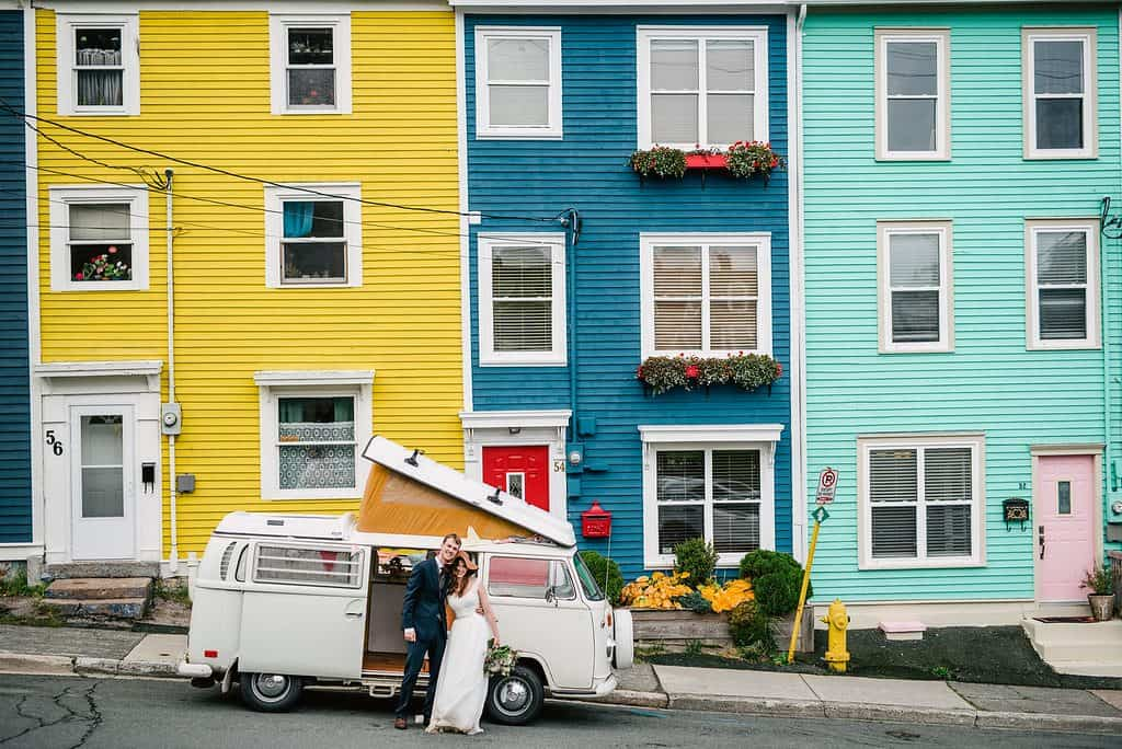 a wedding couple stands in front of a volkswagen westfalia in front of colourful houses (yellow, blue, teal) on jellybean row, downtown st. john's, nl
