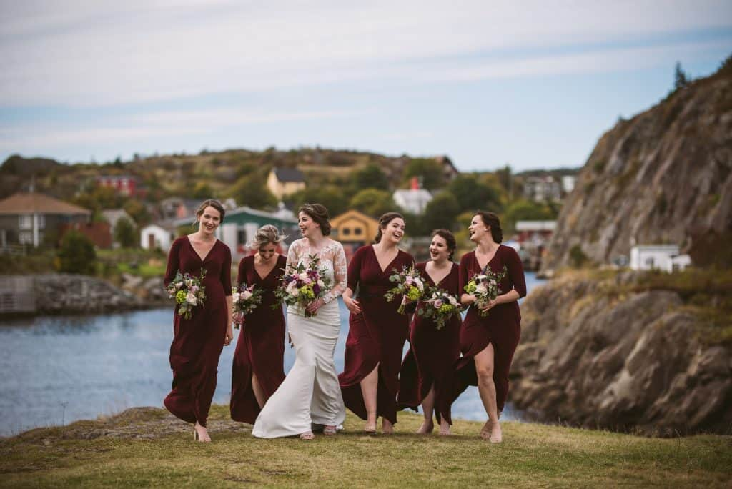 A bride and bridesmaids are walking on a grassy field with Quidi Vidi Village in the background. Some of them are not wearing shoes. They are all holding bouquets and wearing maroon dresses. They are all laughing and looking at each other.