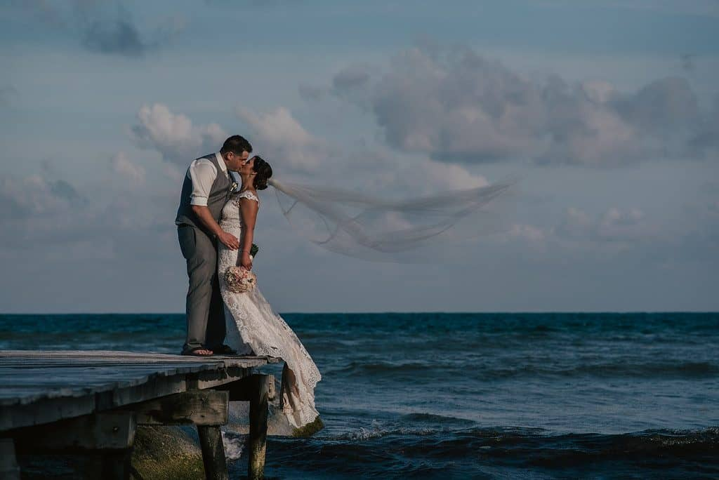 A couple stands on the edge of the greying wharf. The bride's veil is blowing in the wind, puffy clouds are behind them and the ocean is a bright, bright blue.