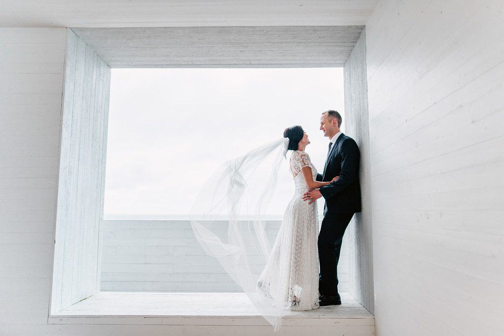 A wedding couple are on the deck of the Fogo Island Inn, looking at each other while the bride's long veil is blowing. The deck is built in such a way that they are inside a square cut-out with a grey sky behind.