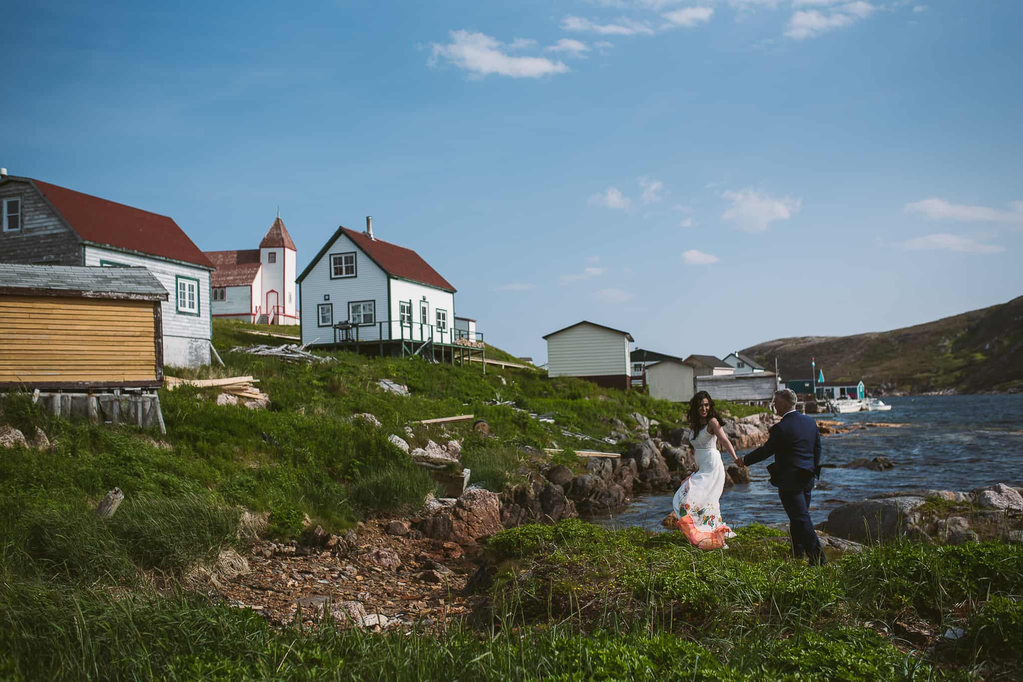 the couple laughs as they walk across the 'beach' near the tiny houses of battle harbour
