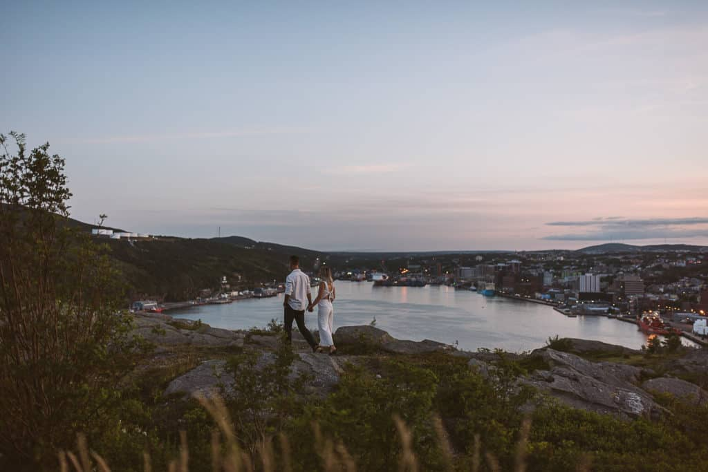 a couple walks along a cliff with the narrows of st johns in the background