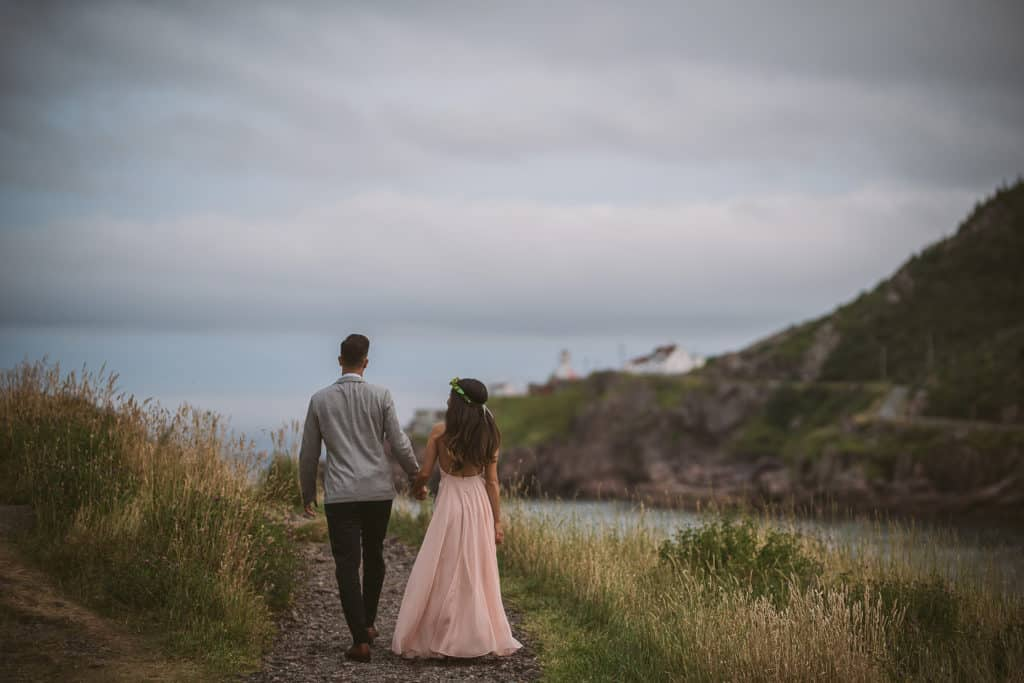 a couple walks away from the camera on a trail in a grassy field. she's wearing a flowy pink dress and has a flower crown, and he is wearing a grey jacket. a red and white lighthouse is visible in the background.