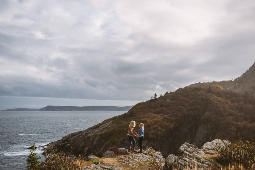two women stand on a ledge overlooking the ocean, holding hands. one is wearing a brown leather jacket and the other is wearing a jean jacket. The window is blowing their hair.