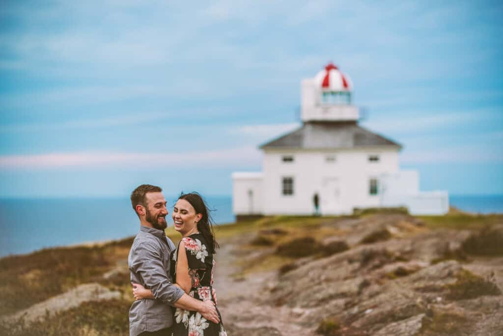 a couple laughs while the wind blows at the lighthouse on cape spear